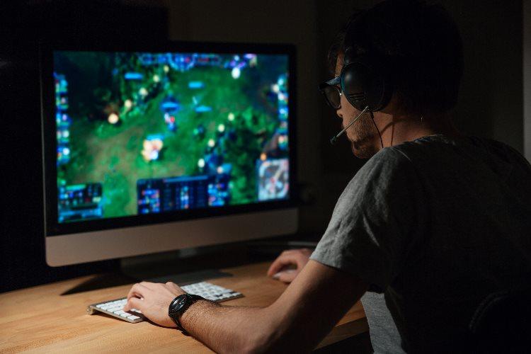 Un hombre juega con su ordenador.